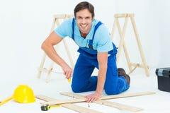 Happy repairman fixing screw on plank Stock Photo