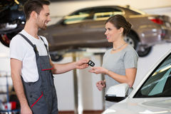Happy repairman giving car key to woman in workshop Stock Photos
