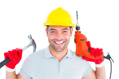 Happy repairman holding hammer and drill machine Royalty Free Stock Images