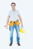 Happy repairman holding spirit level and hardhat Royalty Free Stock Images