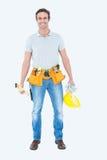 Happy repairman holding spirit level and hardhat Royalty Free Stock Images