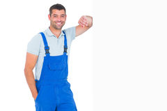 Happy repairman leaning on blank placard. Portrait of happy repairman leaning on blank placard over white background Stock Images