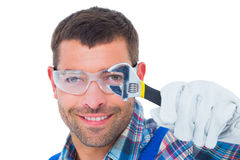Happy repairman looking through wrench Royalty Free Stock Photography