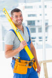 Happy repairman in overalls holding spirit level in office Royalty Free Stock Photos