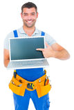 Happy repairman pointing at laptop Stock Images