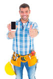 Happy repairman showing mobile phone white gesturing thumbs up Royalty Free Stock Image