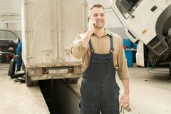 Happy Repairman Talking On Phone. Young handsome male auto technician standing in service garage with broken trucks, talking on smartphone and smiling cheerfully Stock Photo