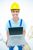 Happy repairman wearing hard hat while holding laptop Stock Images