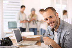 Happy reporter using laptop at office Royalty Free Stock Photo