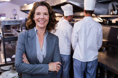 Happy restaurant manager standing with arms crossed in commercial kitchen Royalty Free Stock Photos