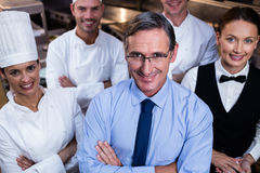 Happy restaurant team standing together with arms crossed in commercial kitchen Royalty Free Stock Photography