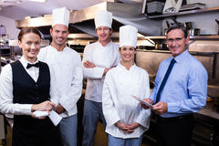 Happy restaurant team standing together in commercial kitchen. Portrait of happy restaurant team standing together in commercial kitchen stock photo