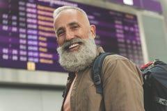 Happy retire standing near timetable Stock Photo