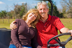 Happy Retired Couple. Good-looking retired couple riding their property in an all terrain utility vehicle Royalty Free Stock Images