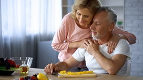 Happy retired couple hugging at home kitchen, love and harmony, cooking leisure stock photography