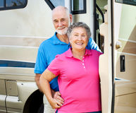 Happy Retired Couple with RV. Happy retired couple posing in the doorway of their luxury motor home Royalty Free Stock Photo