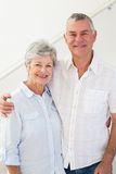 Happy retired couple standing and smiling at camera Stock Photography