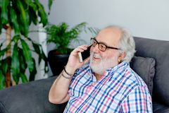 Happy retired man speaking with a mobile in his home Stock Images