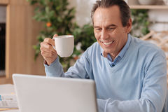 Happy retired man using electronic gadget at home stock photo