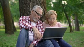 Happy retired man and woman sitting on grass and watching movie on laptop pc