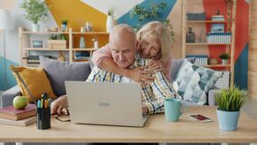 Happy retired people using computer talking hugging expressing love and care