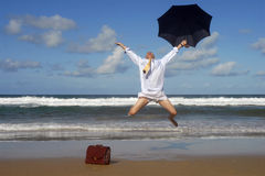 Happy retired senior business man jumping with freedom on a beach vacation. Businessman jumping with happiness and freedom on a beautiful beach.  Copy space Royalty Free Stock Photos