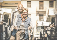Happy retired senior couple having fun with bicycle at flea market. Happy senior couple having fun with bicycle at flea market - Concept of active playful royalty free stock photo