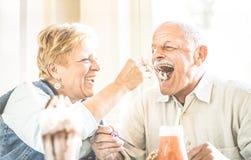 Happy retired senior couple in love enjoying bio icecream cup stock photography