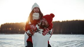 Boy carrying his girfriend on his back. Happy young couple dating in winter outside at Xmas, holidays concept. Family