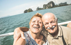 Happy retired senior couple taking travel selfie around world. Active elderly concept with people having fun together at Phang Nga bay Thailand Royalty Free Stock Images