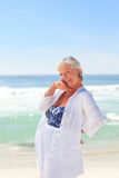 Happy retired woman on the beach Stock Image