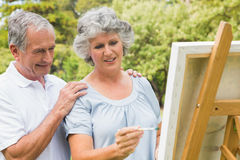 Happy retired woman painting on canvas and talking with husband Royalty Free Stock Photography