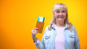 Happy retiree lady showing passport and tickets, travel agency advertisement stock images