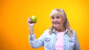 Happy retiree vegetarian lady showing juicy green apple, organic food, dieting stock photos