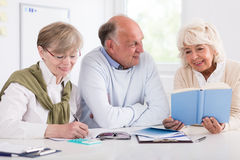 Happy retirees studying. Smiling happy retirees studying at the desk stock images