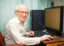 Happy Retirement. Smiling happy old man sitting near computer and holding mouse Royalty Free Stock Photo