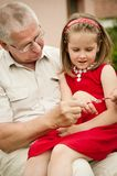 Happy retirement - grandparent with grandchild. Happy retirement - grandparent playing with grandchild, girl sitting on knees Royalty Free Stock Image