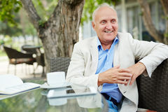 Happy retirement. Positive senior businessman sitting in cafe Stock Photography