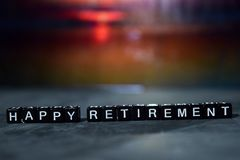 Happy retirement on wooden blocks. Cross processed image with bokeh background royalty free stock photo