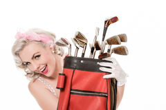 Happy retro girl peeking out from behind red golf bag, isolated Royalty Free Stock Image