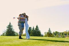Happy reunion of soldier with family outdoors. Military man embracing his family on the park lawn stock photography