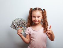 Happy rich kid girl holding money and showing thumb up sign royalty free stock image