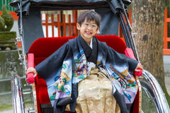 Happy Rickshaw Boy in Kimono. A very happy boy dressed in a formal kimono sits in a rickshaw at a Japanese shrine; this 7-year-old is here for the 7-5-3 Ceremony stock photo