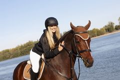 Happy rider caressing horse Stock Photos