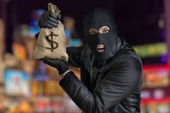 Happy robber is showing stolen bag full of money at night Royalty Free Stock Images
