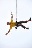 Happy rock climber hanging on rope. Pulled up by another climber Stock Image