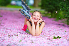 Happy roller girl lying in pink petals, spring garden Royalty Free Stock Photos