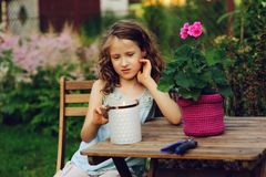 Happy romantic child girl dreaming in evening summer garden decorated with candle stock photo