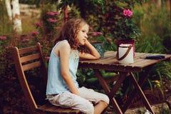 Happy romantic child girl dreaming in evening summer garden stock images