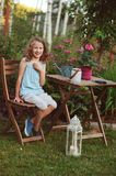 Happy romantic child girl dreaming in evening summer garden Stock Photo